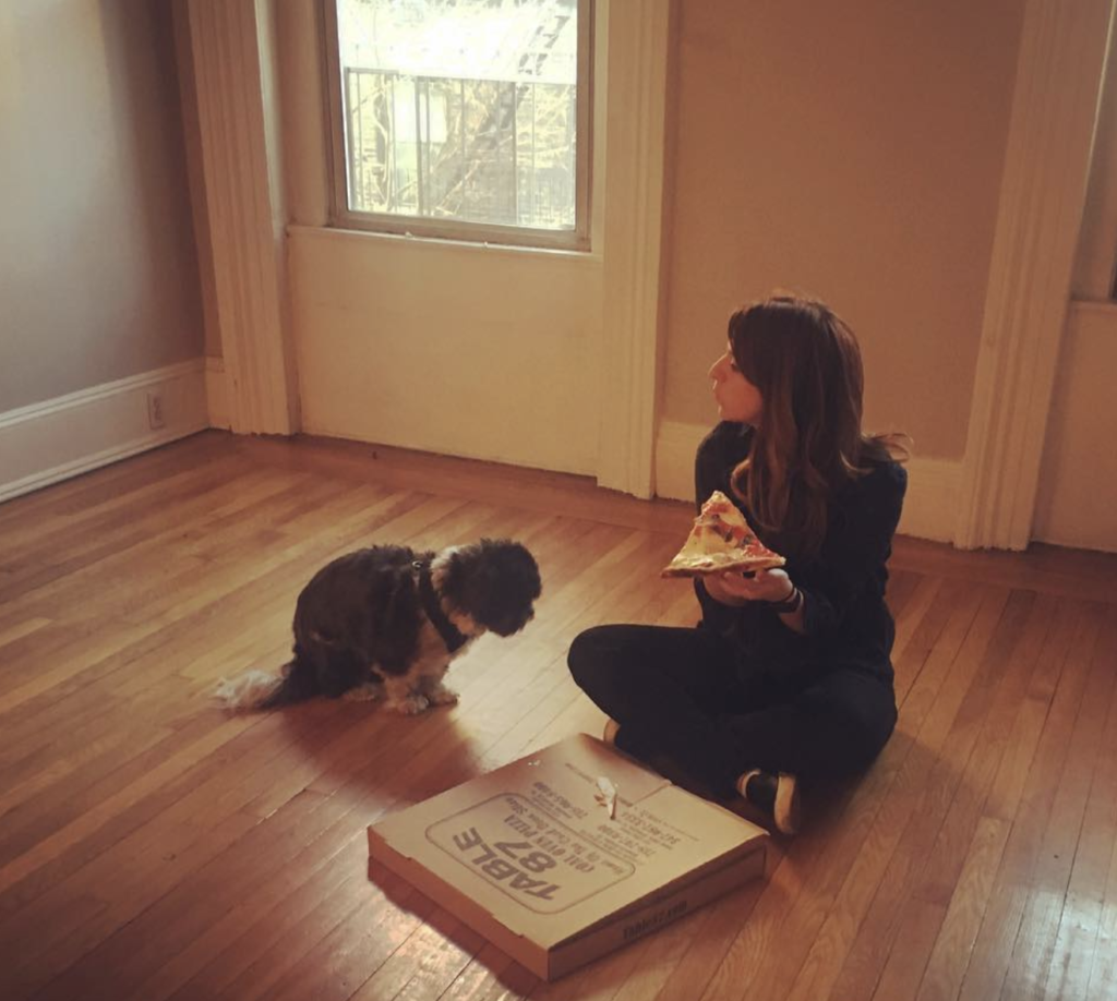 Amy eats pizza with her pup