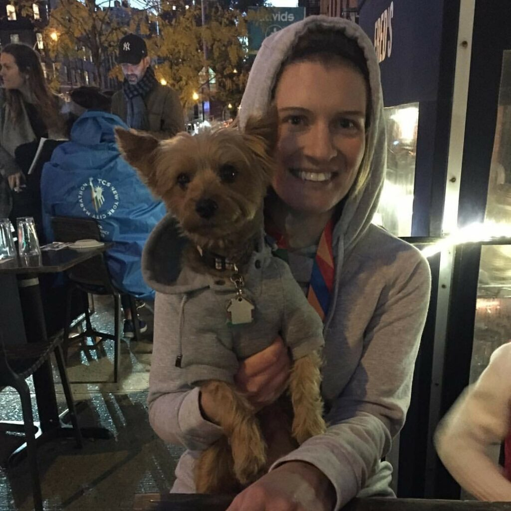 Bridget Runner Spotlight  A woman sits at an outdoor table in a grey hoodie with a race medal around her next, holding a small Yorkie-poo dog, also in a grey hoodie.