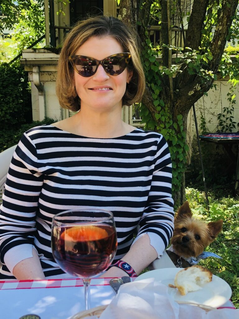 Bright & Wilson - A woman in a striped top with a bob haircut and sunglasses sits outside at a restaurant, with her dog peeking over her arm at the food on the table.