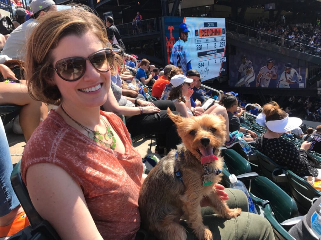 A woman wearing sunglasses and a pink/orange shirt smiles at the camera while holding a dog at a baseball game.
