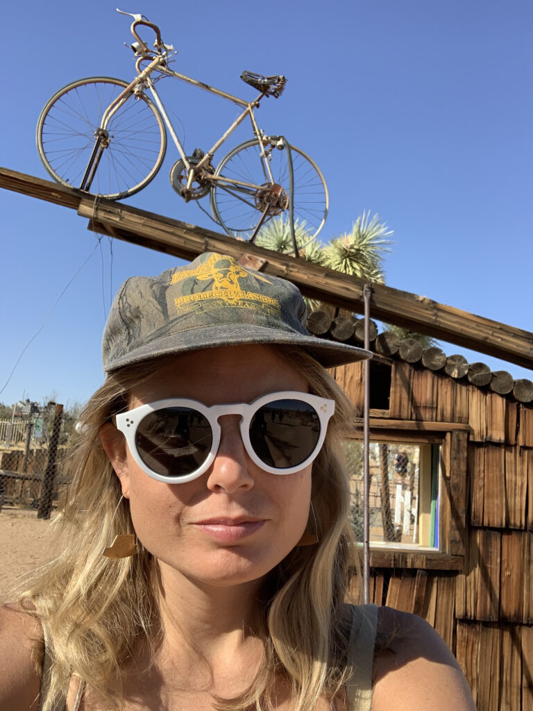 A woman with blonde hair, round white sunglasses, and a grey hat poses outdoors, under a sculpture with a bicycle.
