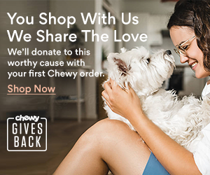 Chewy promotion - A woman with brown hair and glasses holds a white dog and they both look at each other.