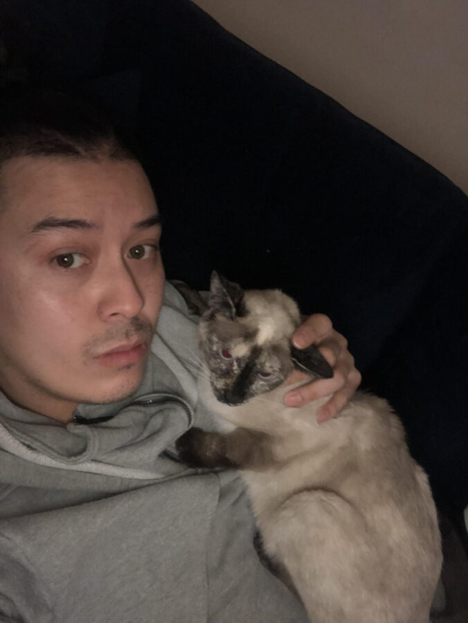 Antonio, with dark hair and eyes, lounges on a couch with his cat Ivy, a Siamese cat who is looking off to the side. Antonio is the Development Manager at PAWS NY.