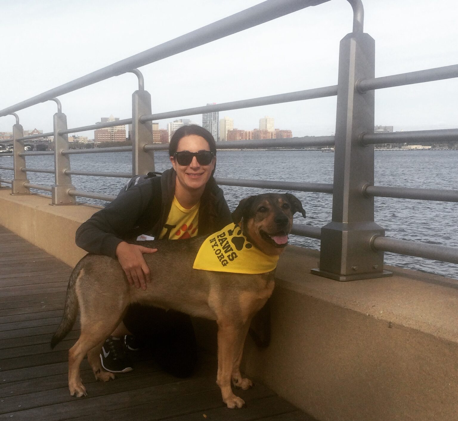 Carrie, with dark hair, sunglasses, and wearing a PAWS NY t-shirt, crouches down next to her dog, Emmylou, who is wearing a PAWS NY bandana. They are on a pier with the river in the background. Carrie is the Deputy Director of Programs and Strategy for PAWS NY