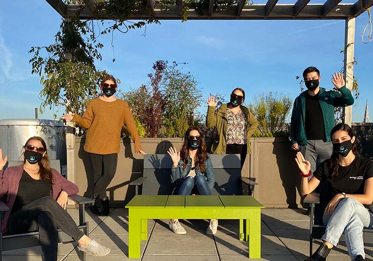 People - Six people alternate between sitting and standing outdoors on a rooftop. Everyone is wearing PAWS NY masks and waving at the camera.